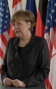 Merkel vor US-Flaggen - Screenshot © bundeskanzlerin.de